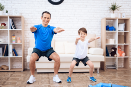 Father doing a workout with his son at home so they can stay active indoors.